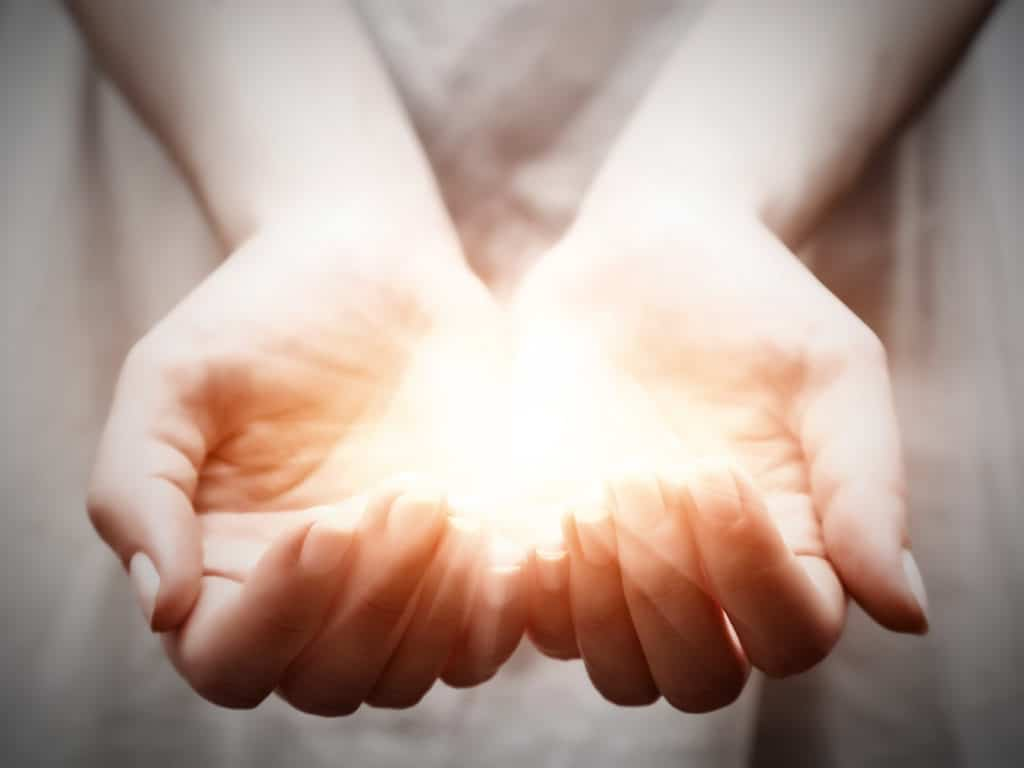 The light in young woman hands in cupped shape. Concepts of sharing, giving, offering, taking care, protection